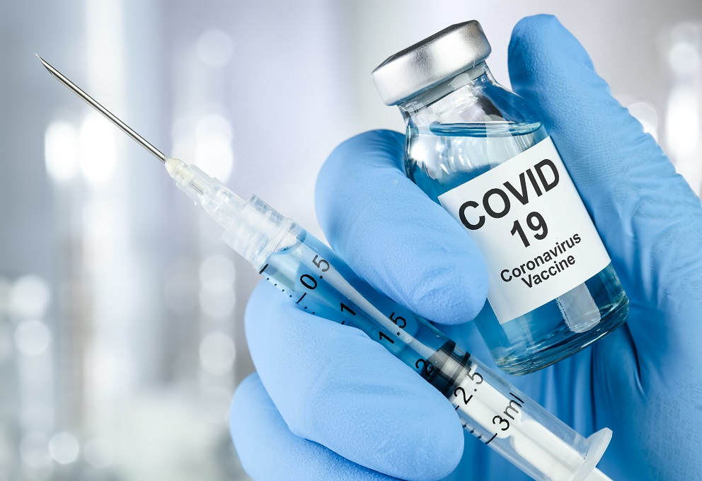 Healthcare cure concept with a hand in blue medical gloves holding Coronavirus, Covid 19 virus, vaccine vial
